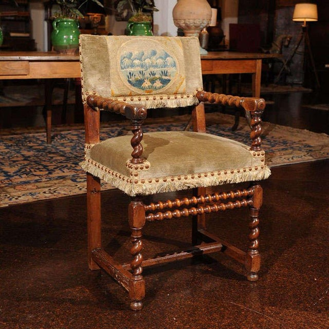 A French Walnut Armchair with carved barley twist arms and leg fronts, a pair of bobbin-turned front stretchers, a square...