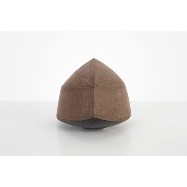 This partially glazed dark brown stoneware sculpture combines all the building block shapes of geometry. Depending on the...