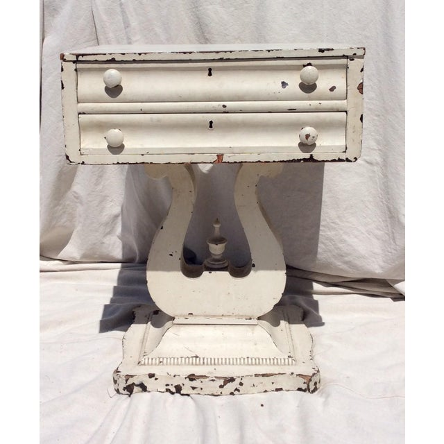 This is a really fun distressed side table with two drawers and an empire leer form base. The old white paint is chipped...