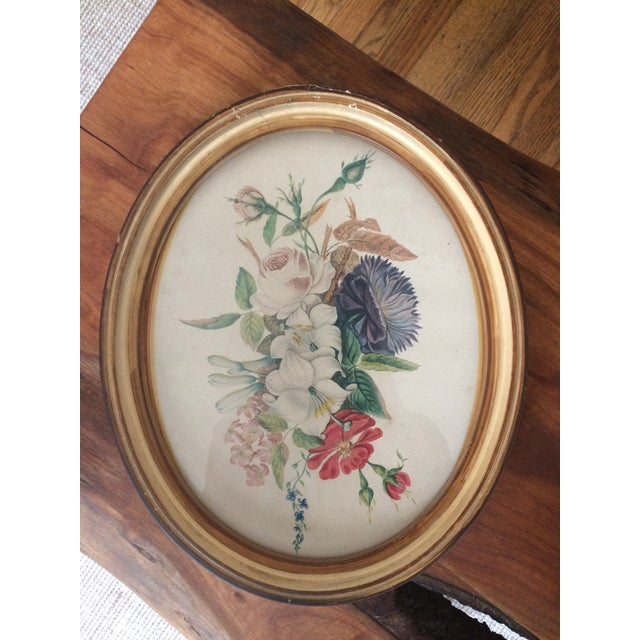 This is a vintage oval framed art print of flowers. This sweet piece is perfect for your bare walls.