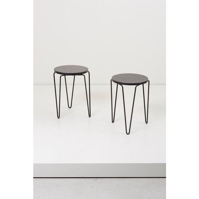 Pair of Classic three-legged stools or side tables with round top and lacquered wrought iron hairpin legs designed by...