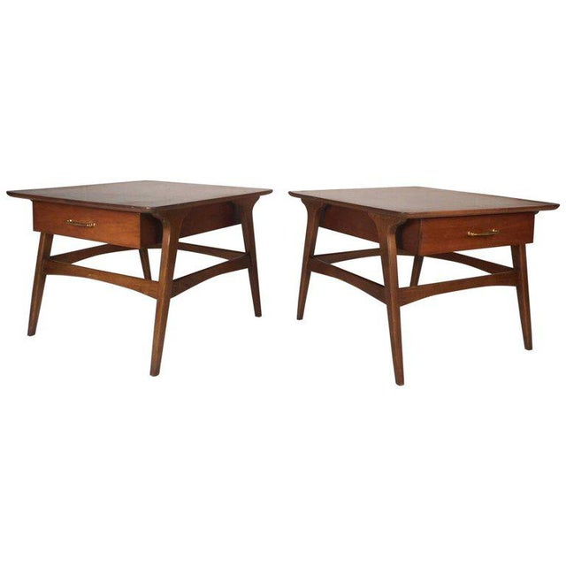 Beautiful pair of vintage modern end tables with a wide square top and angled legs. This unique pair features one large...