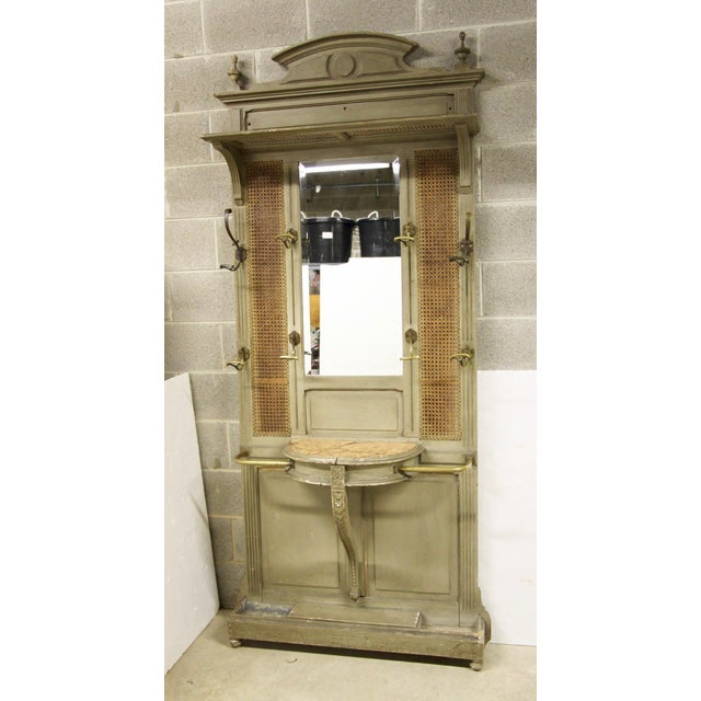 Handsome Louis XVI painted hall tree. Features a marble top demilune, brass railings, caned panels, beveled mirror and...