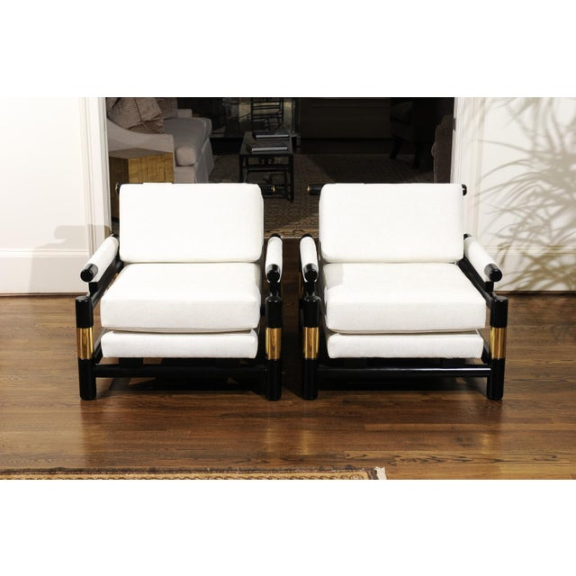 An absolutely jaw-dropping pair of meticulously restored club chairs by Baker, circa 1980. Stout, expertly crafted solid...