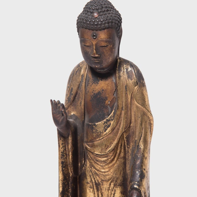 Decorated with black lacquer and gold leaf, this elegant Buddha sculpture was carved from wood in 1875 during Japan's...
