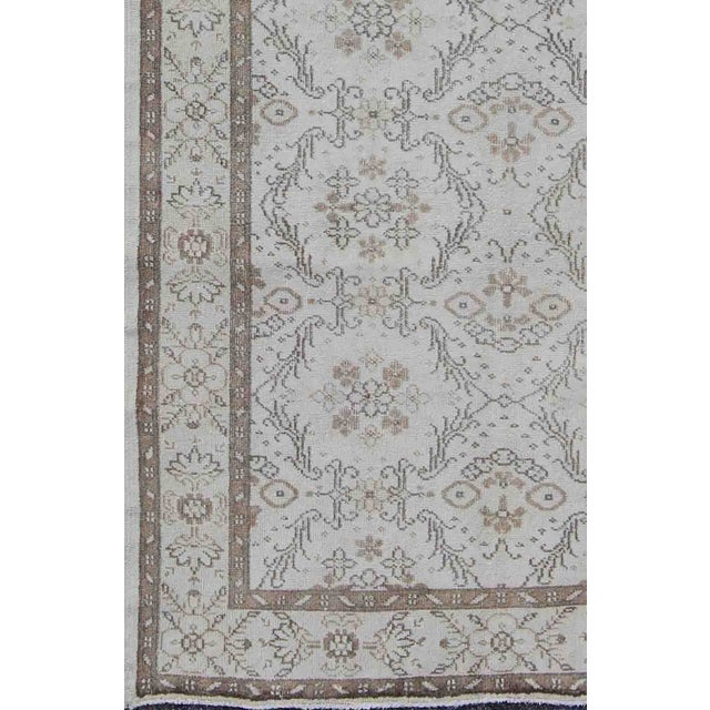 The design of this beautiful vintage Oushak rug from mid-20th century Turkey is enhanced by its lustrous wool. The faint...