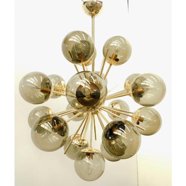 Italian chandelier shown in 18 smoky Murano glass globes mounted on polished brass frame, designed by Fabio Bergomi / Made...
