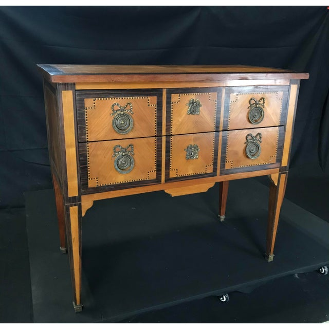 An exquisite inlaid petite commode on stand having an intricate marquetry top and body above two locking drawers with...