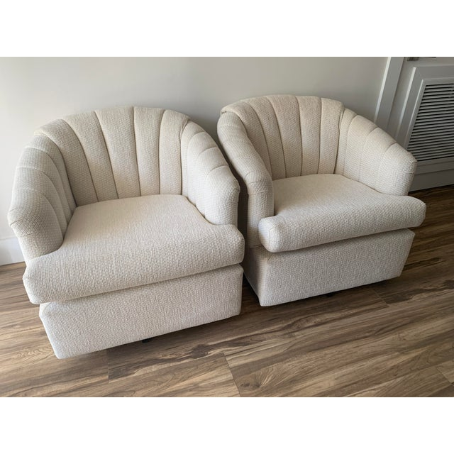Pair of swivel club chairs featuring channel back upholstery in a textured white fabric. Super comfortable and in very...