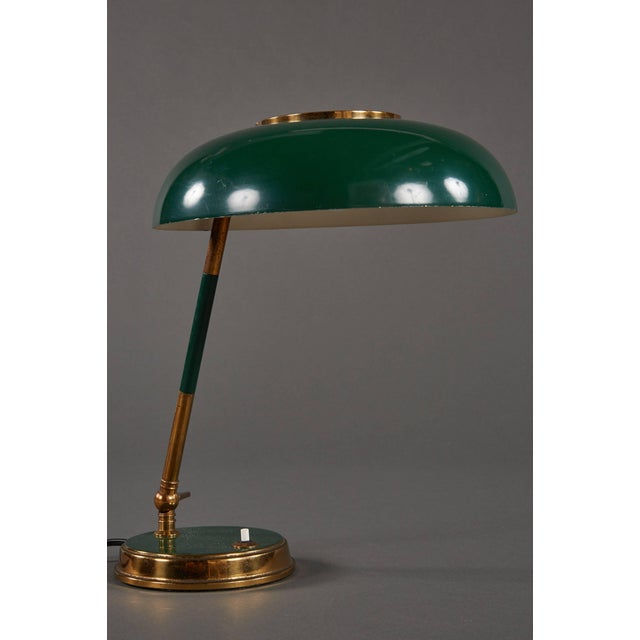 A graceful and stunning Oscar Torlasco table lamp For Lumi, featuring an adjustable green and white painted shade with...