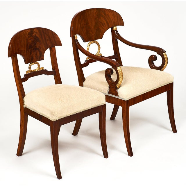 A dining room set of Karl Johan featuring six chairs and two arm chairs in Cuban flamed mahogany with shovel-shaped...