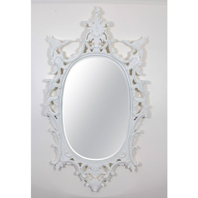 The oval mirror plate within an elaborately hand-carved surround painted chalky white and surmounted by a foliate clasp...