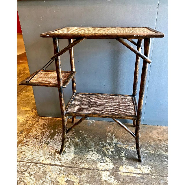 This is a charming late 19th c. or early 20th c. English tortoise shell bamboo and cane pastry table with drop down shelf....