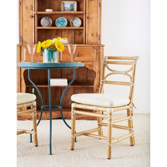 Distinctive set of six bamboo rattan dining chairs made by McGuire. Constructed from thick bamboo rattan poles and...