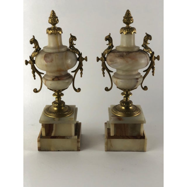 These classical urns consist of stacked layers of marble supporting the urns and are handsomely accented with bronze mounts.