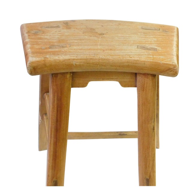This is a simple natural wood single seat wood stool with fan shape seat and vintage wear off patina. Made in China....