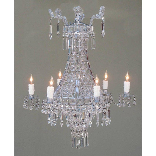 An early 20th century Italian neoclassical crystal and tole chandelier, circa 1900, featuring a basket shaped body woven...