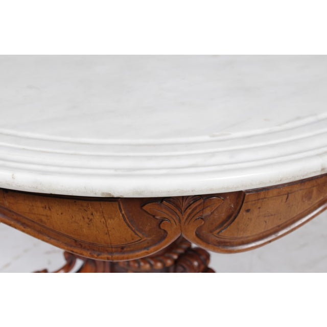 1850s Rococo-Style Victorian center table featuring the popular Tudor Rose design on the base, a round white marble top,...