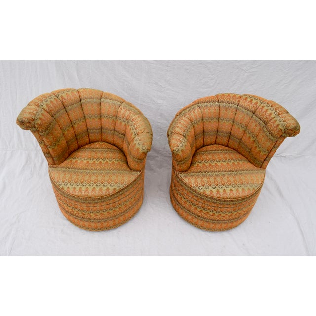 A striking pair of Art Deco inspired swivel, fanned & channel back Nautilus style chairs. Original earth tones upholstery...