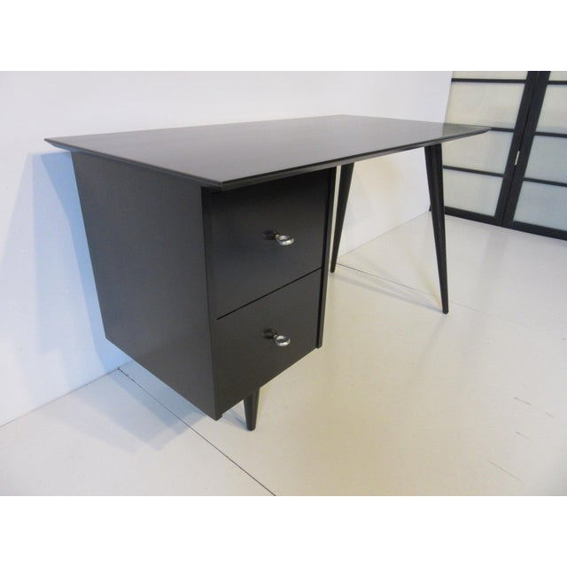 A satin black solid maple McCobb desk with splay leg design, two drawers with early styled machined aluminum ring pulls...