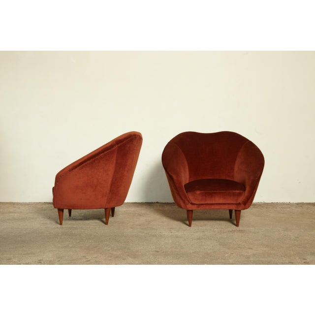 A pair of rust red velvet lounge chairs, designed by Federico Munari (also sometimes attributed to Ico Parisi). The chairs...