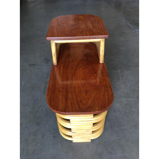 Two-tier stacked rattan end table pair with cut-out sides and mahogany wood top, circa 1930. All pieces listed are...
