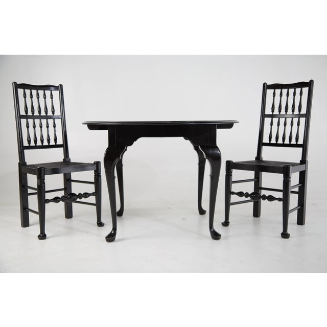 Pair of two Colonial Revival style chairs and Queen Anne style round table that have been refinished in a high gloss black...