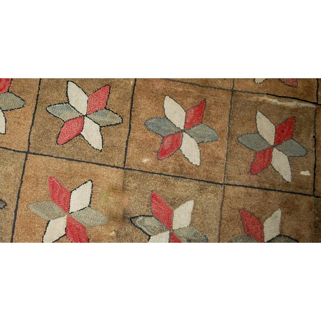 Handmade antique American hooked rug in good condition. The rug made in repeating floral/ geometric pattern: flowers in...