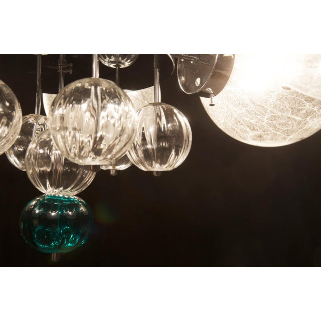 - Big chandelier with chrome frame - Six large handblown globes with air inclusions and 20 small glass balls - Fitted with...