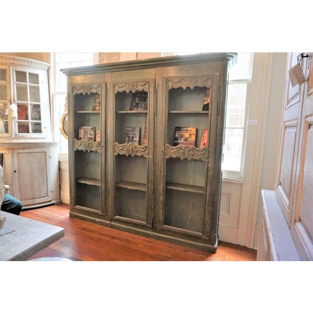 Very long and narrow French bookcase with three chicken wire doors, painted in green . Carving in shells and swags motif.