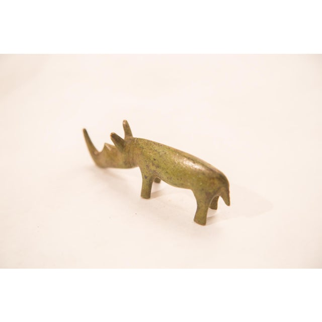 :: Vintage handmade bronze African sculpture of a rhinoceros with a slightly light green patina and subtle details, such...