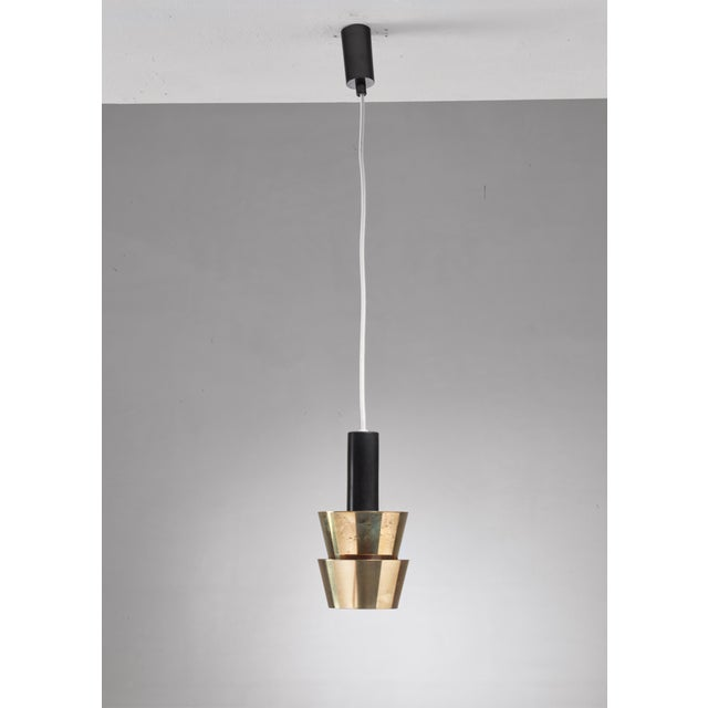 A pendant lamp by Itsu, Finland. The lamp has two brass tapering rings that are connected on the inside, hanging from a...