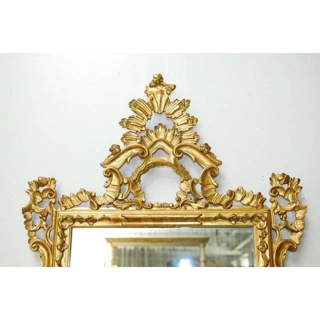 Opulent 19th century Italian hand-carved Rococo style gilt mirror featuring a highly carved crest. Rectangular form...