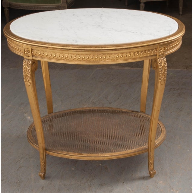 This graceful oval giltwood occasional table, c. 1880, is from France and features a white marble top with delicate grey...