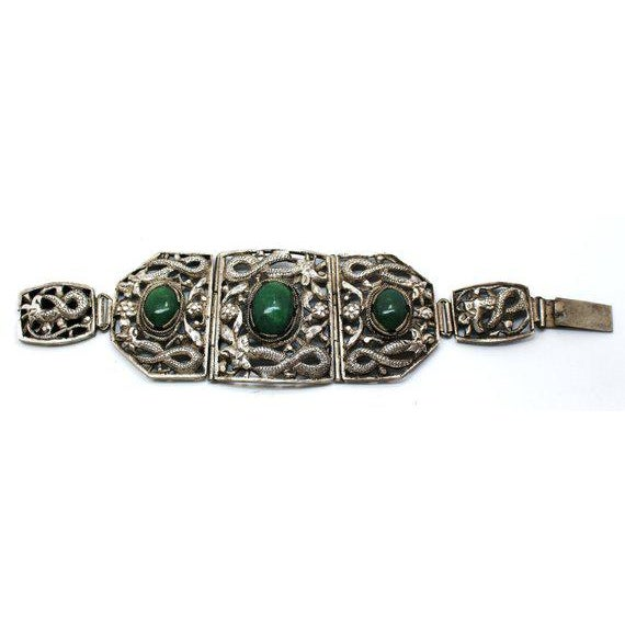 Circa 1930s to 1940s ornately designed, Chinese artisan-made bracelet with bezel set oval serpentine cabochons. The...