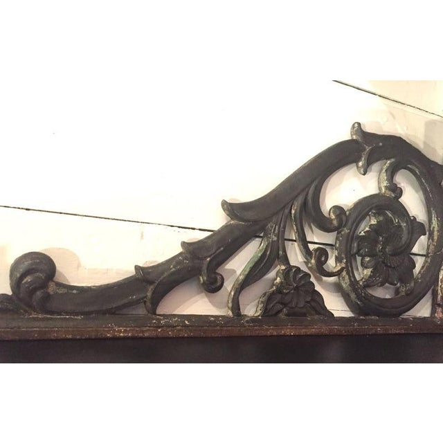Large ornate cast iron bracket with traces of old paint. Could be used as a bracket for a sign or installed to be used as...