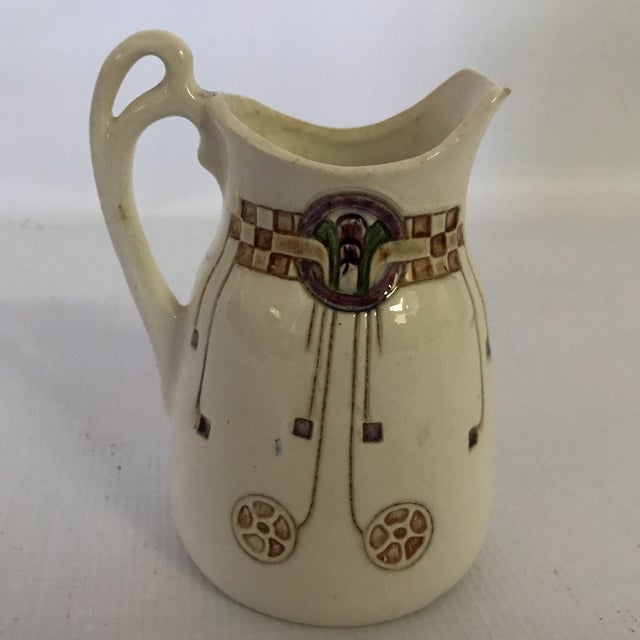 Antique art nouveau ceramic creamer or pitcher wit hand painted decoration.
