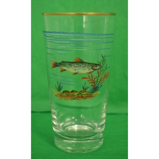 This is a set of 4 vintage highball glasses from the mid 20th century. There's a fish motif on each glass.