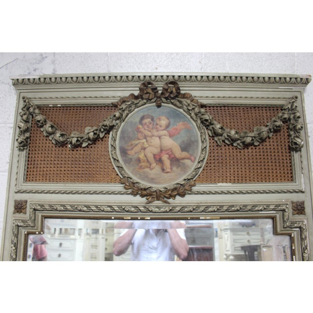 Oil painted French Trumeau mirror with angel motif mounted on wicker backdrop above original mirror plate. All original...