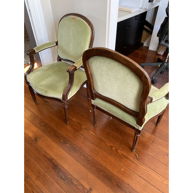 A pair of 18th Century Walnut fauteuils upholstered in light green cotton velvet. Trimmed in a corresponding gimp. Arched...