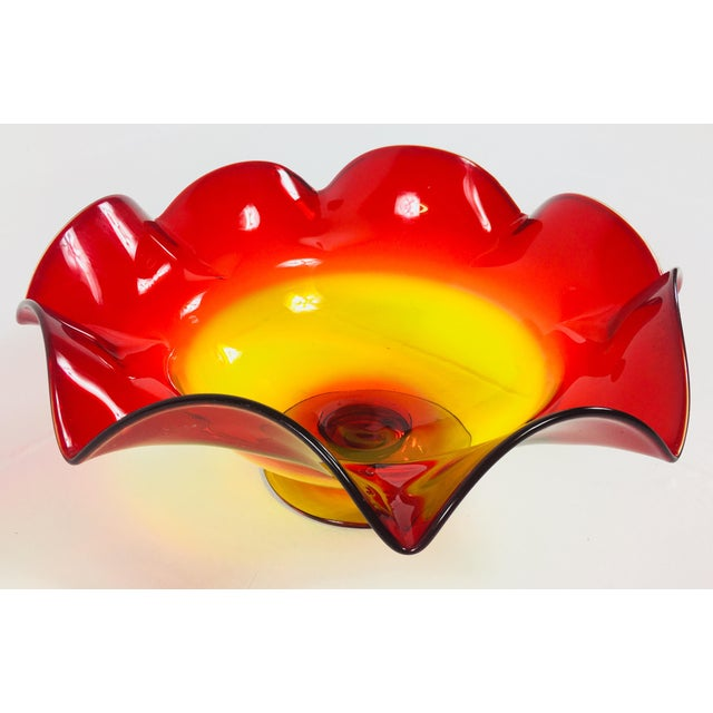 Vintage hand blown Blenko glass bowl with a wavy rim in amberino rouge and gold color. Circa 1960