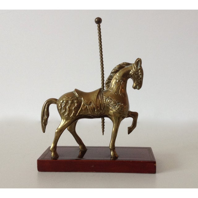 A vintage, brass carousel horse bookend, accent mounted on a pm oxblood red wood base, with inlaid brass banding to...
