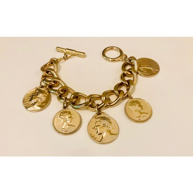 Striking faux coin charm bracelet, circa 1980s . 5, double sided coins hang on a large link gold tone metal bracelet....