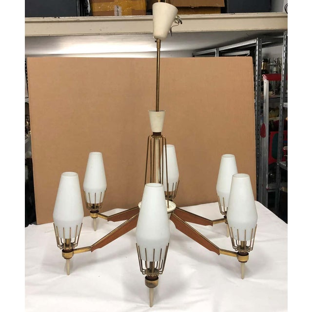 A Mid-Century Modern Italian six lights chandelier, brass it's in original patina, teak, white glass and ivory painted...