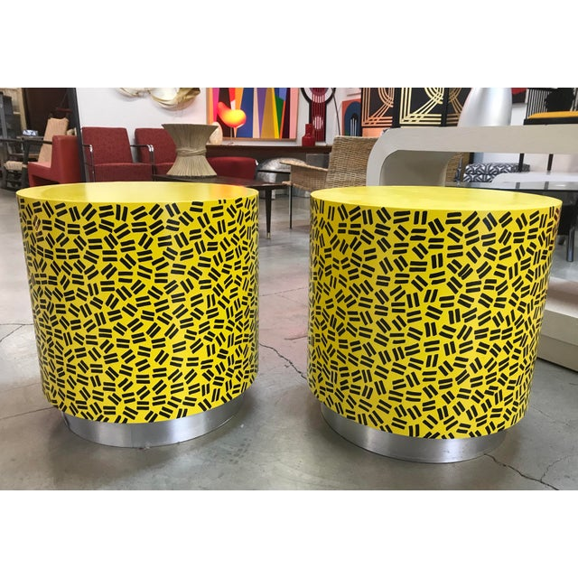 Amazing pair of heavy cylindrical side tables featuring a hand painted design reminiscent of Keith Haring and the pop art...