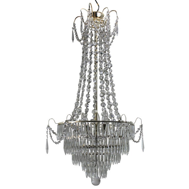 A pair of Swedish chandeliers of simple design in silver plate and hung delicately throughout with cut glass.