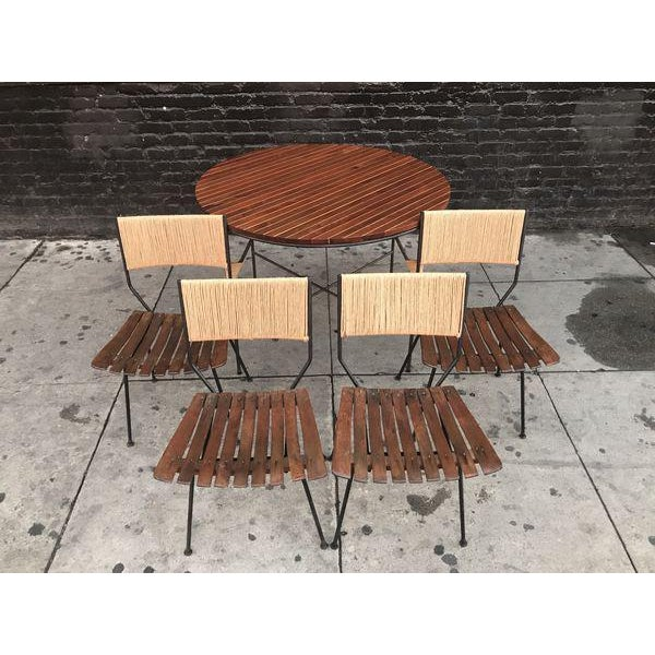 Stunning mid century modern dining set designed by Arthur Umanoff for Raymor Furniture. The table was made with wrought...