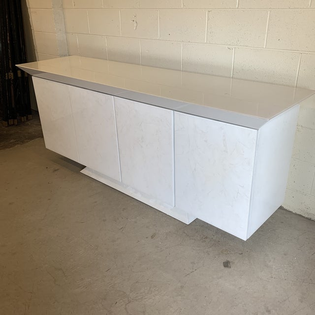 Massive credenza made of wood and white mottled white finish veneer. The white finish has a marbled or giant paint brush...