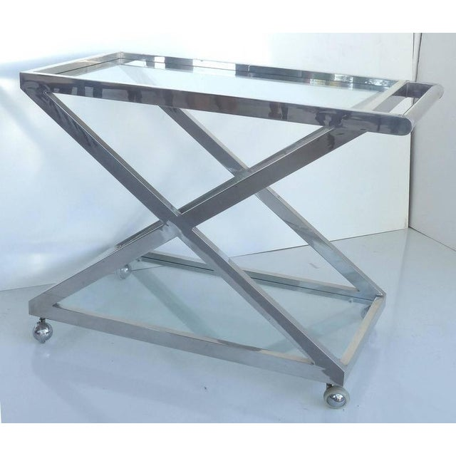 """A striking """"X-form"""" nickel-plated bar or tea trolley with inset glass surfaces above and below. The cart rolls nicely on..."""