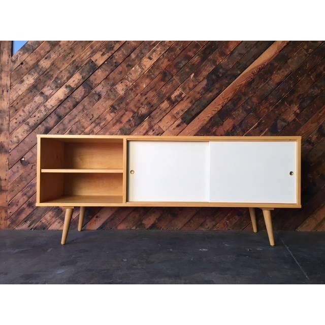 A newly built, maple wood credenza with plenty of interior storage shelving, sliding doors, and 2 drilled holes on the...